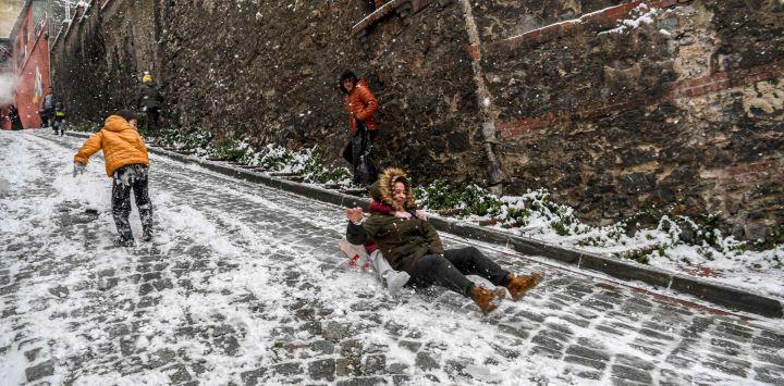 Niños se deslizan en una calle nevada en el distrito de Balat de Estambul.