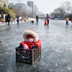 Un hombre tira a un niño sentado en una caja en un río helado en Beijing. | Foto:Wang Zhao / AFP