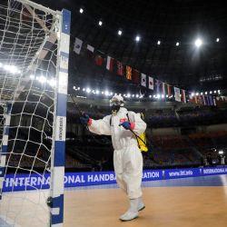 Un empleado de la cancha desinfecta la portería después del partido del Campeonato Mundial Masculino de Balonmano 2021 entre los equipos del Grupo II Japón y Argentina en el Palacio de Deportes del Estadio de El Cairo en la capital egipcia. | Foto:Mohamed Abd El Ghany / POOL / AFP