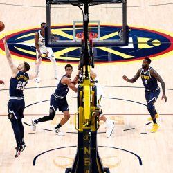 Mike Conley de los Utah Jazz dispara sobre Isaiah Hartenstein de los Denver Nuggets en Ball Arena en Denver, Colorado. | Foto:Jamie Schwaberow / Getty Images / AFP