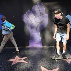 La gente camina y patinan más allá de un mural de Black Lives Matter en Hollywood Boulevard en Los Ángeles, California. | Foto:Mario Tama / Getty Images / AFP