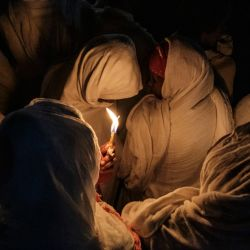 Los fieles cristianos ortodoxos etíopes rezan con velas en el recinto de Fasilides Bath durante la celebración de Timkat, la Epifanía de Etiopía, en la ciudad de Gondar, Etiopía. | Foto:Eduardo Soteras / AFP