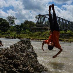 Los estudiantes que regresan a casa de la escuela juegan en un río que ha crecido debido a las recientes lluvias estacionales, en una aldea remota en Panca, provincia de Aceh. | Foto:CHAIDEER MAHYUDDIN / AFP