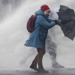 Una manifestante antigubernamental utiliza un paraguas para protegerse del chorro de un cañón de agua durante una manifestación en la Plaza de los Museos. | Foto:Robin Van Lonkhuijsen / ANP / DPA