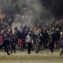Manifestantes tunecinos bloquean una calle durante enfrentamientos con las fuerzas de seguridad en el suburbio de la ciudad de Ettadhamen, en las afueras del noroeste de Túnez, en medio de una ola de protestas nocturnas en el país del norte de África. | Foto:Fethi Belaid / AFP