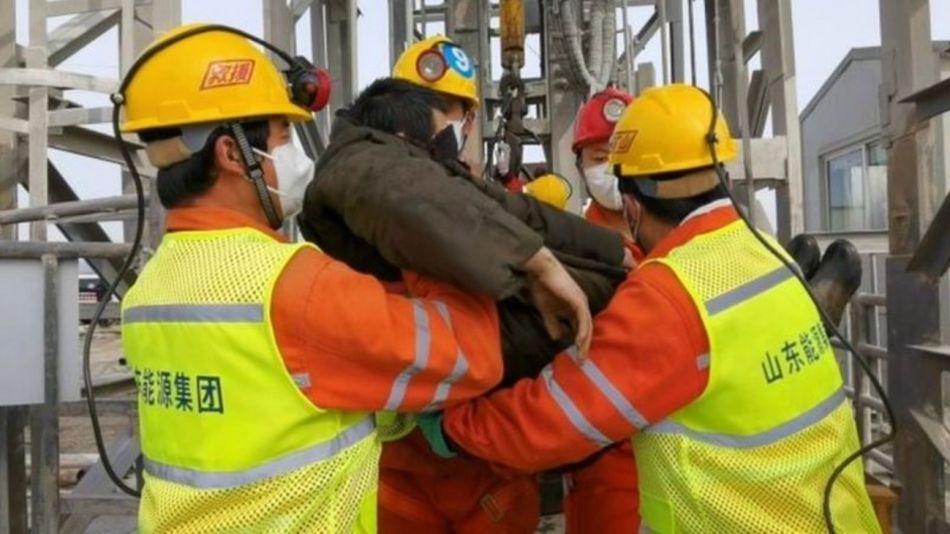 Uno de los mineros rescatados es trasladado por socorristas en la mina de oro de Qixia, en la provincia china de Shandong.