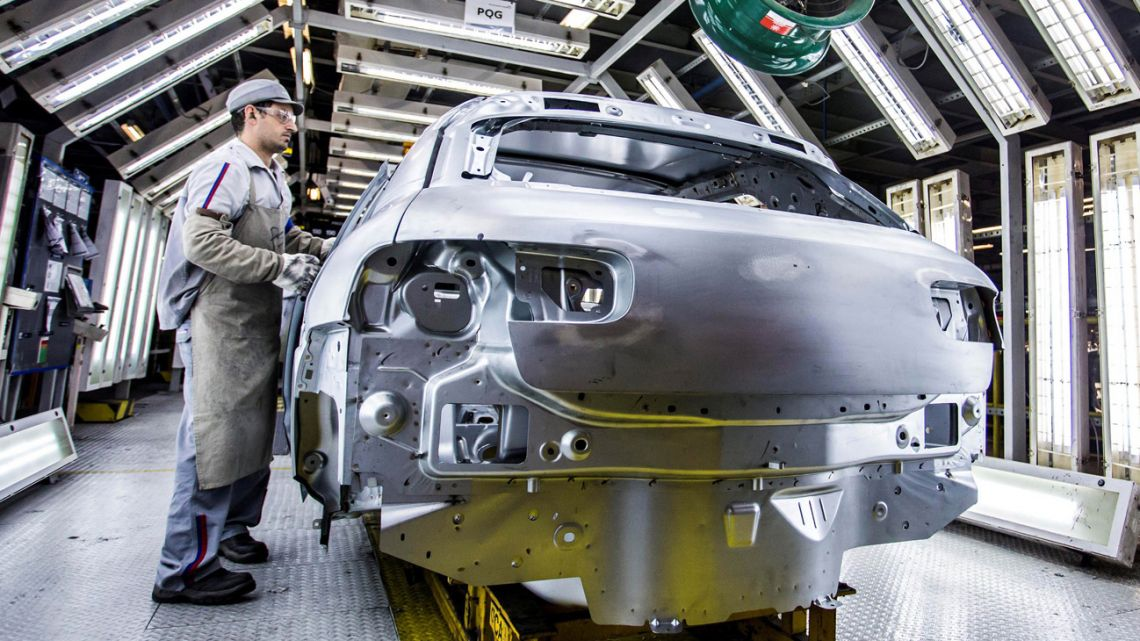 Workers produce automobiles at a car manufacturing plant.
