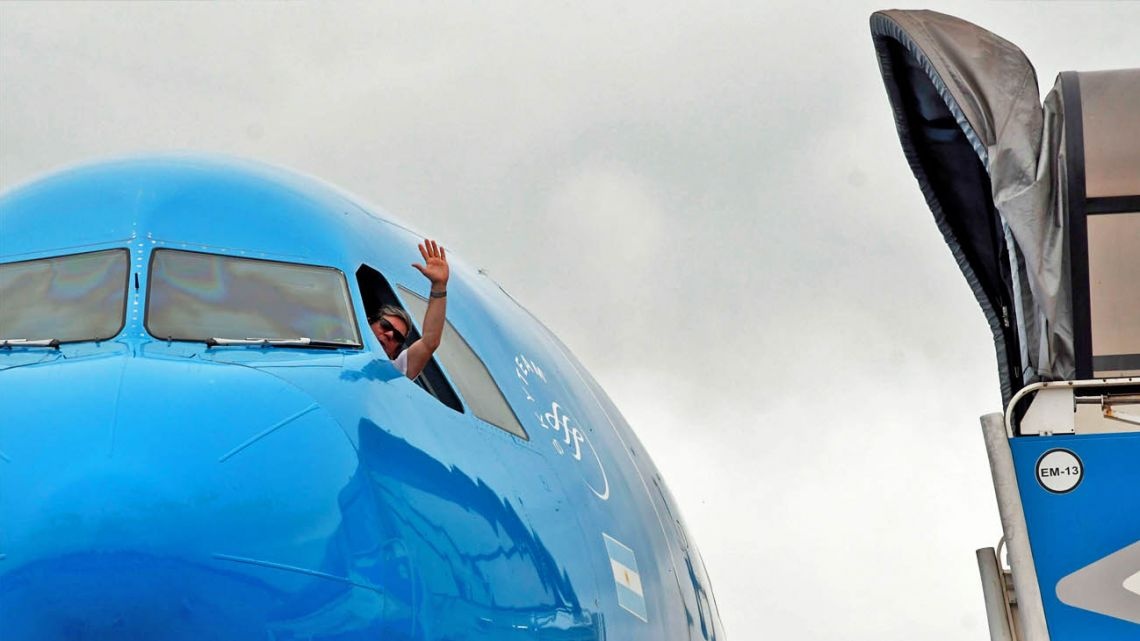 A pilot salutes from a plane.