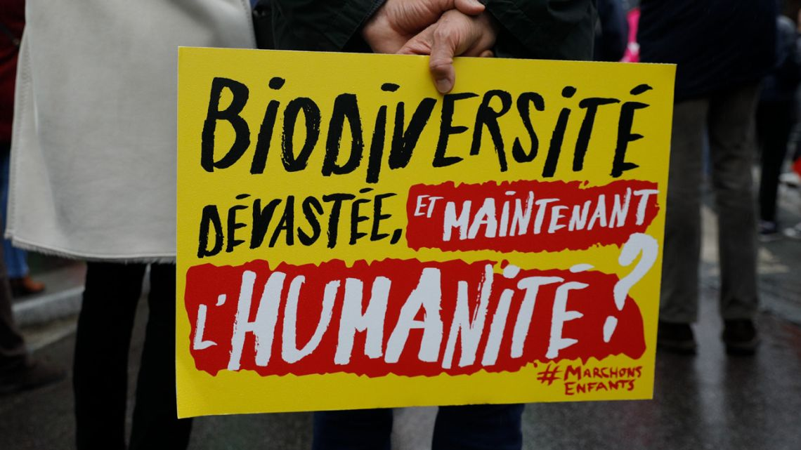 "A demonstrator holds a placard reading ""biodiversity devastated, and now humanity?"", during a demonstration in Paris, on January 31, 2021."