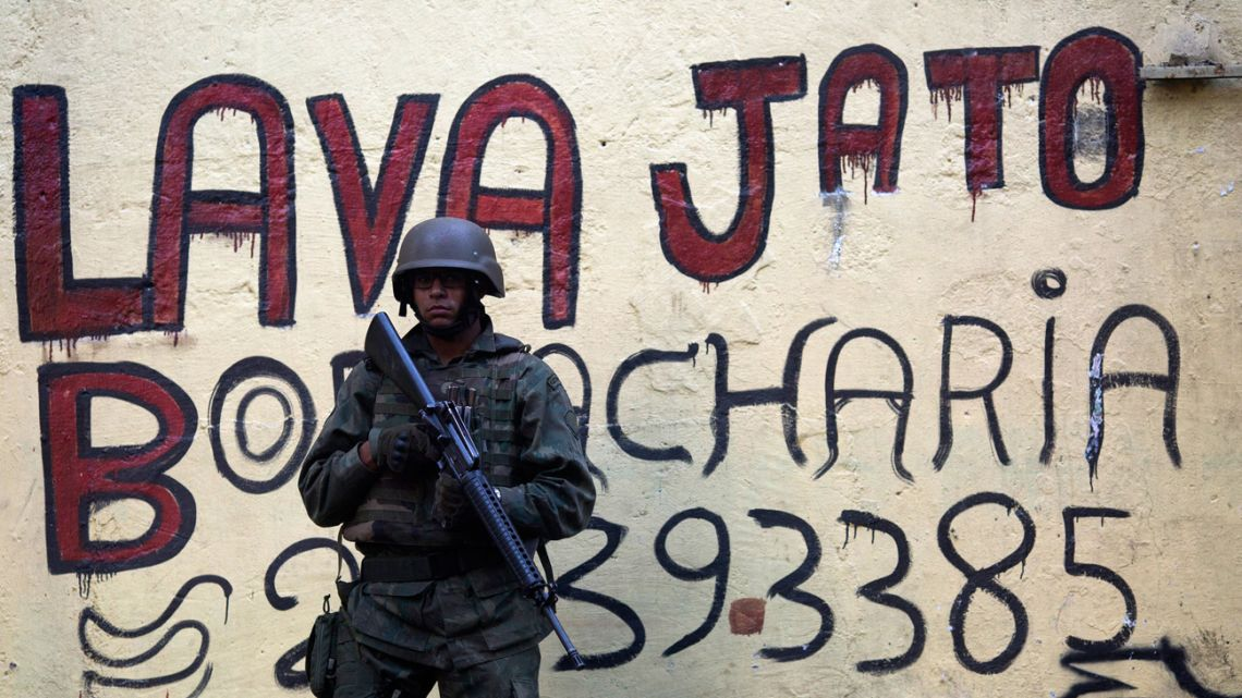 In this file photo taken on September 26, 2017, a Brazilian soldier stands guard in front of a graffiti ardvertising a car wash (Lava Jato), the name of the anticorruption operation that shook up the country, during an operation in the Rocinha favela in Rio de Janeiro, Brazil.
