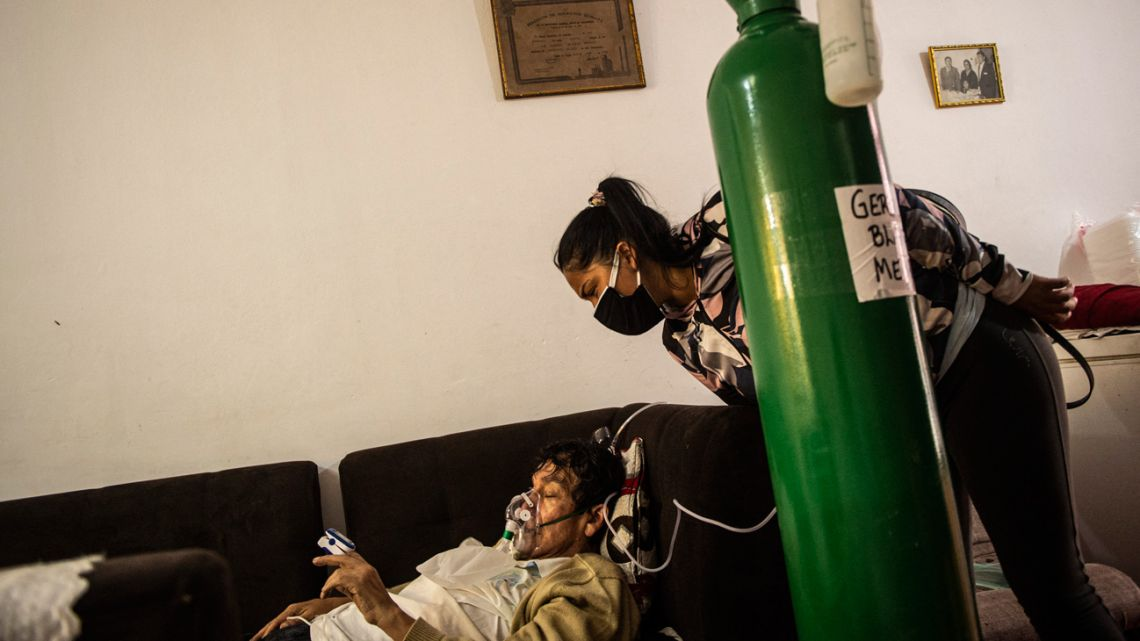 Germán Blanco's daughter July, 30, checks on her father as he lies on a couch in the living room connected to an oxygen tank at his home in Callao, Peru on February 4, 2021.
