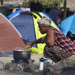 Una mujer cocina cerca de tiendas de campaña en un campamento improvisado establecido por migrantes en Necoclí, Colombia. - Cientos de migrantes están varados en el noroeste de Colombia, luego de que los gobiernos de Colombia y Panamá cerraran fronteras debido a la pandemia de COVID-19, siguiendo una afluencia masiva con destino a América del Norte.   Foto:Raúl Arboleda / AFP