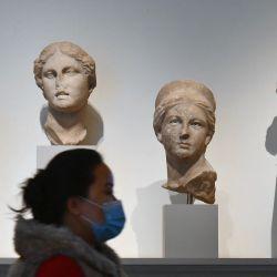 Un visitante con una mascarilla pasa junto a esculturas de piedra en el Museo Metropolitano de Arte, 'The Met' en la ciudad de Nueva York.   Foto:Angela Weiss / AFP