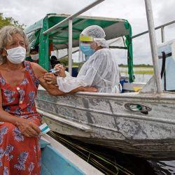 Olga D'arc Pimentel, de 72 años, es vacunada por un trabajador de salud con una dosis de la vacuna COVID-19 de AstraZeneca en la comunidad de Nossa Senhora Livramento en las orillas del Río Negro cerca de Manaus, estado de Amazonas, Brasil.   Foto:Michael Dantas / AFP