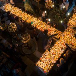 Los creyentes rezan alrededor de una plataforma en forma de cruz cubierta con velas unidas a tarros de miel durante una ceremonia que marca el día de San Haralampi, santo patrón ortodoxo de los apicultores, en la Iglesia de la Santísima Virgen en Blagoevgrad, Bulgaria oriental.   Foto:Nikolay Doychinov / AFP