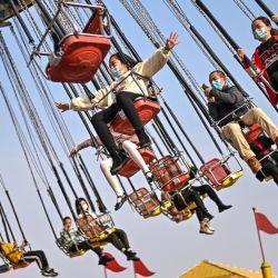 Los visitantes dan vueltas en una de las atracciones en un parque de diversiones en Wuhan en la provincia central de Hubei en China, antes del inicio del Año Nuevo Lunar. | Foto:Hector Retamal / AFP