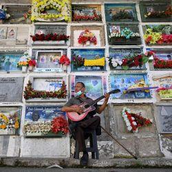 Javier Giraldo, de 57 años, músico que ha tocado su guitarra durante 30 años en entierros, es visto en el cementerio de Buenaventura, Colombia.   Foto:Luis Robayo / AFP