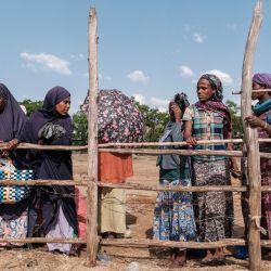 Personas desplazadas internamente, que huyen de la violencia en la zona de Metekel en el oeste de Etiopía, se reúnen durante una distribución de artículos por una organización no gubernamental internacional en Chagni, Etiopía. | Foto:Eduardo Soteras / AFP