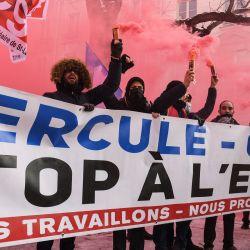 Los manifestantes sostienen bengalas y una pancarta que dice  | Foto:Alain Jocard / AFP