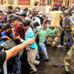 Activistas de izquierda se dispersan mientras la policía ataca con porras durante una protesta contra las diferentes políticas del estado liderado por el Congreso de Trinamool y el gobierno central liderado por el Partido Bharatiya Janata, en Calcuta. | Foto:Dibyangshu Sarkar / AFP