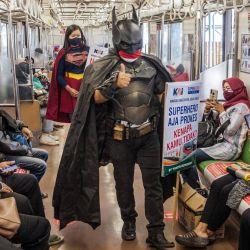Una pareja vestida con trajes de superhéroe caminan por un tren de cercanías para promover la conciencia sobre la salud y prevenir la transmisión del coronavirus COVID-19 en Yogyakarta. | Foto:Agung Supriyanto / AFP