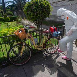 Karla Hitzuri Montano, médico cirujana, vestida con traje protector se aplica sprite desinfectante en sus zapatos antes de ingresar al edificio donde vive uno de sus pacientes que padece el coronavirus COVID-19, en un barrio de la Ciudad de México.   Foto:Claudio Cruz / AFP