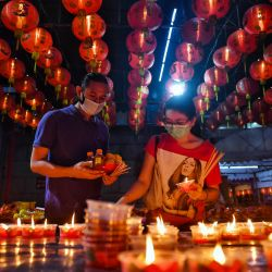 Los fieles encienden velas en el templo Wat Mongkol Samakhom en Chinatown en Bangkok, antes del inicio del Año Nuevo Lunar, que marca el comienzo del Año del Buey. | Foto:Lillian Suwanrumpha / AFP