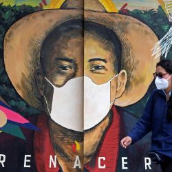 Una mujer con máscara facial camina junto a una pared pintada en Bogotá, Colombia.   Foto:Raúl Arboleda / AFP
