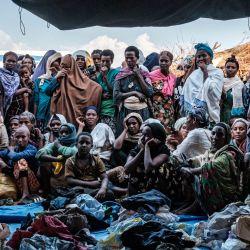 Personas desplazadas internamente (IDP), que huyen de la violencia en la zona de Metekel en el oeste de Etiopía, se reúnen fuera de una tienda donde se distribuye ropa en un campamento en Chagni, Etiopía. | Foto:Eduardo Soteras / AFP