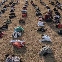 Una persona desplazada, que huye de la violencia en la zona de Metekel en el oeste de Etiopía, se sienta entre pilas de ropa que se distribuye en un campamento en Chagni, Etiopía.   Foto:Eduardo Soteras / AFP