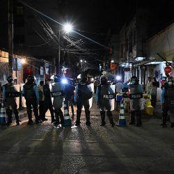 Policías antidisturbios bloquean una calle mientras al menos nueve policías acusados de estar involucrados en la muerte de un estudiante de enfermería, abandonan la sede de Medicina Forense en Tegucigalpa.- Keyla Martínez, de 26 años, falleció en una celda de la Policía Nacional. luego de ser capturado en el municipio de La Esperanza por violar un toque de queda impuesto por el gobierno en medio de la pandemia de COVID-19. | Foto:Orlando Sierra / AFP