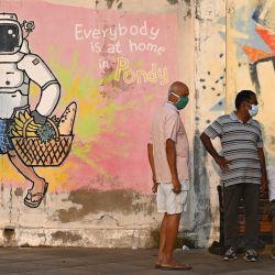 La gente se sienta cerca de un mural en una colonia francesa en Pondicherry. | Foto:Punit Paranjpe / AFP