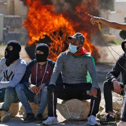 Los manifestantes palestinos se reúnen frente a neumáticos en llamas en medio de enfrentamientos con las fuerzas israelíes tras una manifestación contra los asentamientos en la aldea de Deir Jarir, cerca de Ramallah, en la Cisjordania ocupada.   Foto:Abbas Momani / AFP