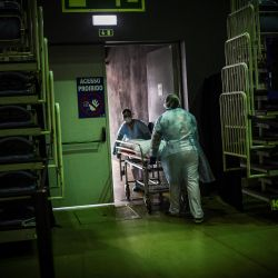 Trabajadores de la salud llevan el cuerpo de una víctima de Covid-19 en camilla en el pabellón deportivo Portimao Arena convertido en hospital de campaña para pacientes de Covid-19 en Portimao, en la región del Algarve. | Foto:Patricia De Melo Moreira / AFP