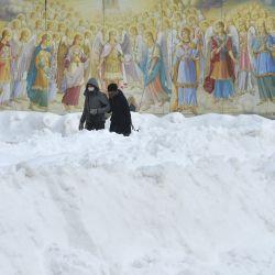 Una pareja camina frente a los frescos de la catedral de la cúpula dorada de Mykhaylo mientras las nevadas continúan azotando la capital ucraniana de Kiev.   Foto:Sergei Supinsky / AFP