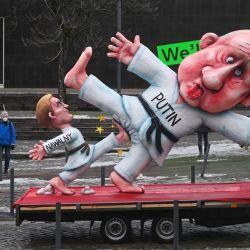 Dos espectadores solitarios observan como una carroza de carnaval que representa al líder de la oposición rusa Alexei Navalny vestido como un judoka pateando las bolas del presidente ruso Vladimir Putin durante una versión reducida del tradicional desfile del Lunes de las Rosas en Duesseldorf. Alemania occidental. | Foto:Ina Fassbender / AFP