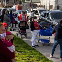 Una mujer salvadoreña sostiene a su sobrina en brazos mientras espera en la fila del Centro de Distribución de Alimentos    Foto:Apu Gomes / AFP