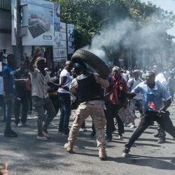 Un manifestante arroja un neumático en llamas a un oficial de policía durante una manifestación en Delmas, cerca de Port-au-Prince. - Varios miles de personas se manifestaron en la capital de Haití, Puerto Príncipe, diciendo que el gobierno estaba tratando de establecer una nueva dictadura y denunciando el apoyo internacional al presidente Jovenel Moise. | Foto:Reginald Louissaint Jr / AFP