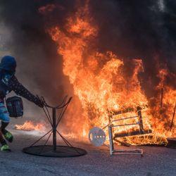 Un manifestante se mueve del fuego durante una manifestación en Port-au-Prince. - Varios miles de personas se manifestaron en la capital de Haití, Puerto Príncipe, diciendo que el gobierno estaba tratando de establecer una nueva dictadura y denunciando el apoyo internacional al presidente Jovenel Moise.   Foto:Reginald Louissaint Jr / AFP