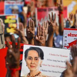 Los manifestantes levantan el saludo de tres dedos con carteles pidiendo la liberación del líder civil de Myanmar detenido Aung San Suu Kyi durante una manifestación contra el golpe militar en Yangon. | Foto:Ye Aung Thu / AFP