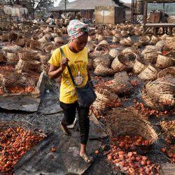 Una señora camina entre cestas llenas de tomates vandalizados después de los enfrentamientos étnicos mortales entre los comerciantes fulani del norte y los yoruba del sur en el mercado de Shasha en Ibadan, en el suroeste de Nigeria. | Foto:Pius Utomi Ekpei / AFP