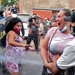 Familiares de internos son rociados por la policía durante enfrentamientos frente a la cárcel de Tacumbu luego de un motín en el que murieron seis internos, en Asunción.   Foto:Norberto Duarte / AFP