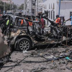 El personal de rescate y los transeúntes se reúnen cerca de los escombros en el lugar de un atentado suicida con coche bomba cerca de un puesto de control de seguridad en Mogadiscio.   Foto:Abdirazak Hussein Farah / AFP