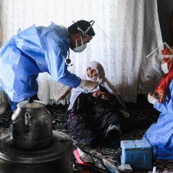 Berfo Arsakay, de 101 años, se prepara para recibir una vacuna del doctor Akay Kaya y la enfermera Yildiz Ayten del equipo de vacunación del hospital público de Bahcesaray, en la aldea. de Guneyyamac en el este de Turquía, como parte de una expedición para vacunar a los residentes de 65 años o más con la vacuna CoronaVac Covid-19 de Sinovac.   Foto:Bulent Kilic / AFP