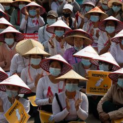 Mujeres de Myanmar con sombrero tradicional ocupan una calle durante una manifestación contra el golpe militar en Mandalay. | Foto:STR / AFP