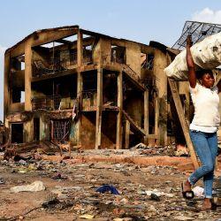 Una mujer lleva mercancías recuperadas de tiendas quemadas mientras pasa frente a un edificio de tres pisos quemado durante los enfrentamientos étnicos mortales entre los comerciantes fulani del norte y los yoruba del sur en el mercado de Shasha en Ibadan, en el suroeste de Nigeria. | Foto:Pius Utomi Ekpei / AFP