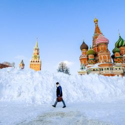 Un hombre pasa junto a una enorme pila de nieve recogida en la Plaza Roja en Vasilyevsky Spusk de Moscú, con la Torre Spasskaya del Kremlin y la catedral de San Basilio al fondo, durante un día helado, después de una serie de fuertes nevadas. | Foto:Yuri Kadobnov / AFP