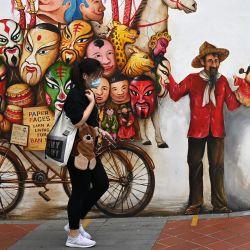 Una mujer pasa junto a un mural en una pared a lo largo de una calle en Singapur. | Foto:Roslan Rahman / AFP