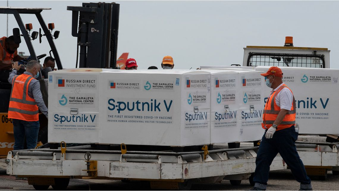 Venezuelan airport workers place in a refrigerated truck packages containing 100,000 doses of the Russian Sputnik V vaccine against the COVID-19 virus at the Simon Bolivar international airport in La Guaria, Venezuela on February 13, 2021.