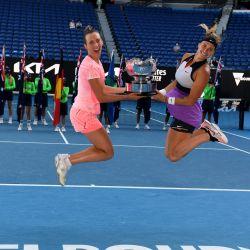 La belga Elise Mertens y su compañera bielorrusa Aryna Sabalenka sostienen el trofeo de los ganadores mientras celebran vencer a las checas Barbora Krejcikova y Katerina Siniakova en su partido final de dobles femenino el día doce del torneo de tenis del Abierto de Australia en Melbourne. | Foto:William West / AFP